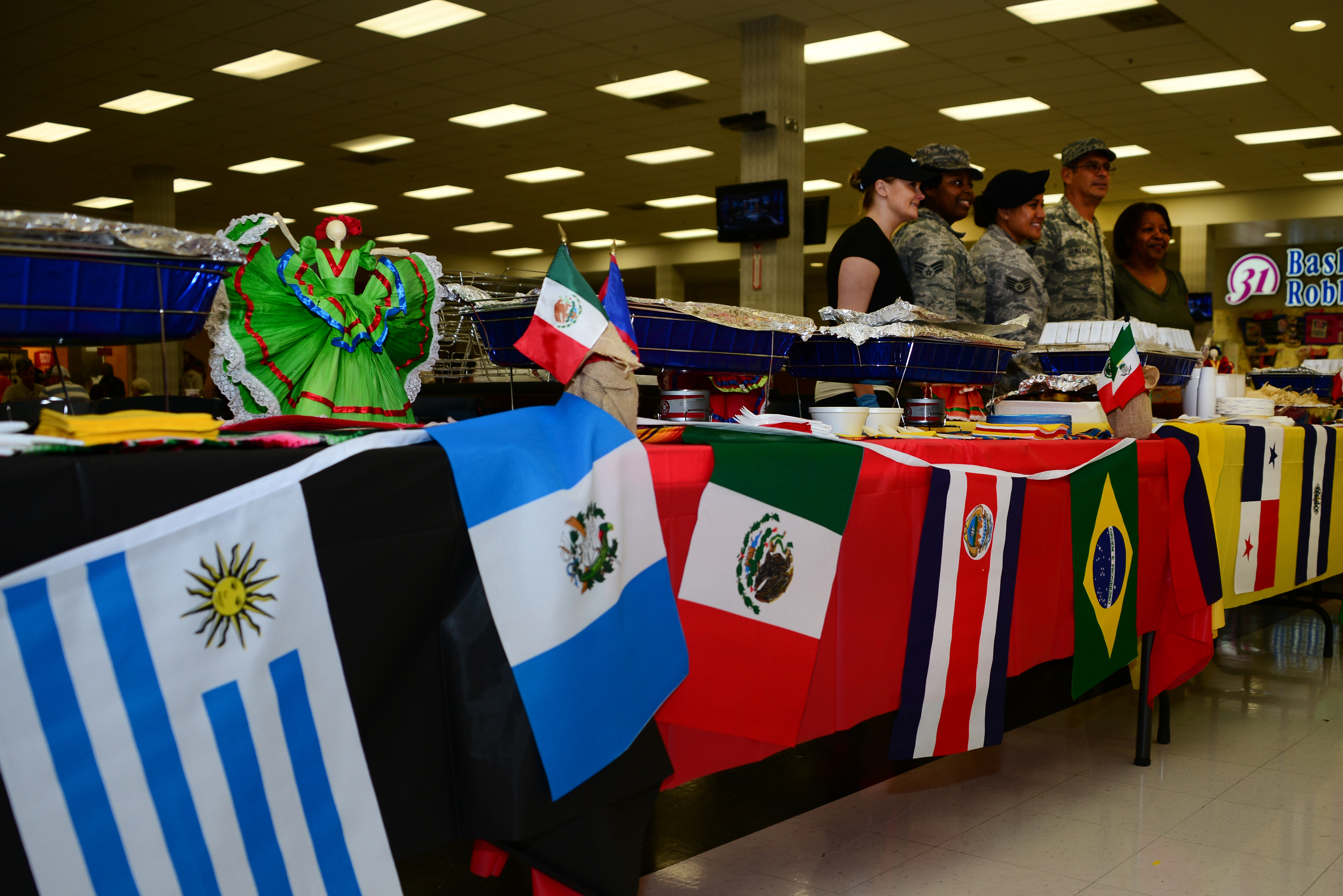 Flags of different Hispanic cultures hang on a table